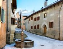 Poca via con le case tipiche e fontana nella più vecchia parte di Guarda, distretto della locanda, cantone svizzero di Graubunden Fotografia Stock