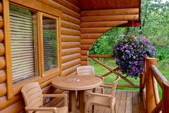 Pocahontas Vacation Cabins, Alberta/Canada - September 2, 2016: Table, chairs, flowers on porch of wooden vacation rental cabin. royalty free stock images