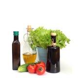Pocas botellas del aceite de oliva con la ensalada verde y las verduras Imagenes de archivo