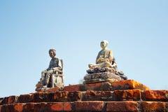 Pocas estatuas de piedra instaladas en una pared de ladrillo en Sukhothai Tailandia fotos de archivo
