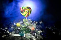Pocas piruletas coloridas del corazón del caramelo en diversos caramelos coloreados contra fondo de niebla entonado oscuro Imagen de archivo libre de regalías