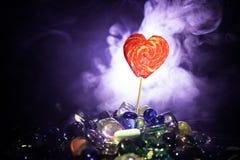 Pocas piruletas coloridas del corazón del caramelo en diversos caramelos coloreados contra fondo de niebla entonado oscuro Imágenes de archivo libres de regalías