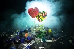 Pocas piruletas coloridas del corazón del caramelo en diversos caramelos coloreados contra fondo de niebla entonado oscuro Foto de archivo libre de regalías