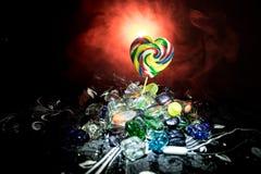 Pocas piruletas coloridas del corazón del caramelo en diversos caramelos coloreados contra fondo de niebla entonado oscuro Imagenes de archivo