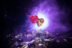 Pocas piruletas coloridas del corazón del caramelo en diversos caramelos coloreados contra fondo de niebla entonado oscuro Imagen de archivo