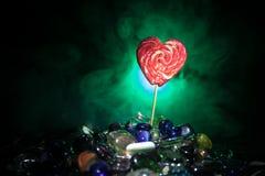 Pocas piruletas coloridas del corazón del caramelo en diversos caramelos coloreados contra fondo de niebla entonado oscuro Foto de archivo