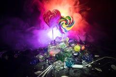 Pocas piruletas coloridas del corazón del caramelo en diversos caramelos coloreados contra fondo de niebla entonado oscuro Fotos de archivo