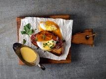 Poché avec le lard et le pain grillé, le persil et les épices sur le papier sur une planche à découper sur un fond gris Photo stock
