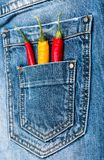 Poche de jeans fournis de personnel avec les poivrons frais rouges et jaunes, fond de denim Secret piquant dans la poche de panta photo stock