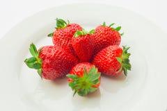 Poche fragole fresche su un piatto bianco Immagine Stock