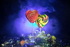 Poche lecca-lecca variopinte del cuore della caramella sulle caramelle colorate differenti contro fondo nebbioso tonificato scuro Immagine Stock