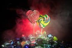 Poche lecca-lecca variopinte del cuore della caramella sulle caramelle colorate differenti contro fondo nebbioso tonificato scuro Immagini Stock