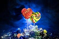Poche lecca-lecca variopinte del cuore della caramella sulle caramelle colorate differenti contro fondo nebbioso tonificato scuro Immagine Stock Libera da Diritti