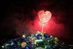 Poche lecca-lecca variopinte del cuore della caramella sulle caramelle colorate differenti contro fondo nebbioso tonificato scuro Fotografie Stock