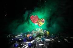 Poche lecca-lecca variopinte del cuore della caramella sulle caramelle colorate differenti contro fondo nebbioso tonificato scuro Fotografie Stock Libere da Diritti