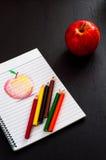Poche matite variopinte sullo sketchbook con lo schizzo rosso della mela di arte di tiraggio della mano su carta allineata sulla  Fotografia Stock Libera da Diritti