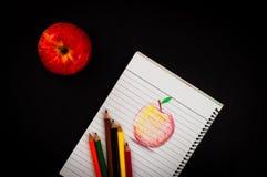 Poche matite variopinte sullo sketchbook con lo schizzo rosso della mela di arte di tiraggio della mano su carta allineata sulla  Immagini Stock Libere da Diritti