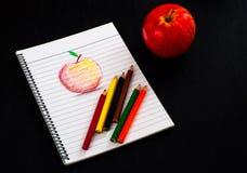 Poche matite variopinte sullo sketchbook con lo schizzo rosso della mela di arte di tiraggio della mano su carta allineata sulla  Fotografie Stock