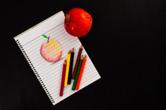 Poche matite variopinte sullo sketchbook con lo schizzo rosso della mela di arte di tiraggio della mano su carta allineata sulla  Fotografia Stock