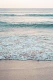 Poche onde nella spiaggia al tramonto Fotografia Stock Libera da Diritti