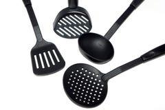 Poche, spatule et ?cumoire de plastique de nourriture dans le noir sur un fond blanc, isolat, ustensiles de cuisine photographie stock libre de droits