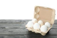 Poche uova crude del pollo in contenitore di cartone sulla tavola di legno immagini stock libere da diritti
