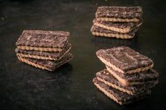 Pochi biscotti del cioccolato in tre pile sul vassoio nero Fotografie Stock