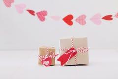 Pochi contenitori di regalo con i cuori che appendono sopra Immagini Stock