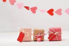 Pochi contenitori di regalo con i cuori che appendono sopra Fotografie Stock Libere da Diritti