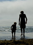 Pochi ragazzi dell'ombra sulla spiaggia Fotografia Stock