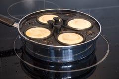 Pochieren von vier Eiern zum Frühstück in Ei-pochierenden Pan 2 lizenzfreie stockfotografie