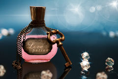 Poción de amor en una botella con la cadena y llave alrededor de la botella imágenes de archivo libres de regalías