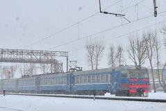 Pociąg pasażerski na kolei rusza się w wielkiej śnieżnej miecielicie obraz royalty free