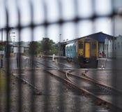 Pociąg przy stacją za poręczami Obrazy Royalty Free
