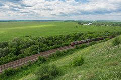 Pociąg towarowy z lokomotywami przechodzi poręczem w Rosja, wzdłuż typowego rosjanina krajobrazu, odgórny widok fotografia stock