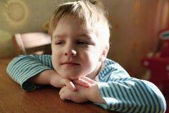 Pocieszny dziecko siedzi przy stołem i spryt spojrzeniami obrazy stock