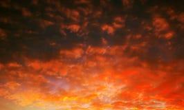 Pocked fiery sky at sunset with sun rays Stock Photos