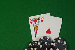 Pocket Ace King suited. Poker, pocket hand Ace King hearts suited with black chips on green felt Royalty Free Stock Photos