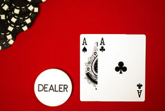 Pocket aces on the button. Poker hand, pocket aces and button with black chips on red felt Stock Images