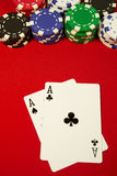 Pocket aces on the button. Poker hand, pocket aces and button with colorful chips on red felt Royalty Free Stock Image