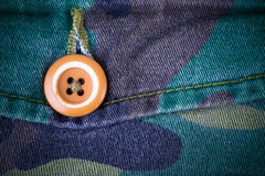 Pocket with a button on the fabric with a camouflage pattern. Ba Royalty Free Stock Images