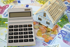 Pocket calculator with blank display. Model of a New building. In the background many euro banknotes and coins Royalty Free Stock Photos