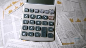Pocket calculator falling and bouncing on papers Stock Photos