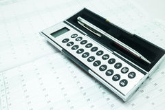 Pocket calculator and pen on the table Stock Photography