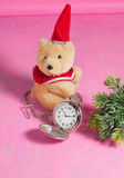 Pocket clock with bear toy on pink Stock Image