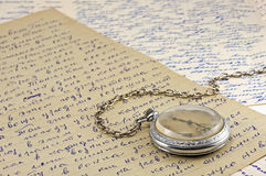 Pocket clock and old letters. Pocket clock on old letters background Royalty Free Stock Images