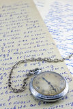 Pocket clock and old letters. Pocket clock on old letters background Royalty Free Stock Photography