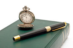 Pocket clock and pen on a book Stock Image
