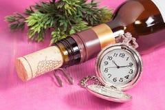 Pocket clock and wine bottle Stock Image