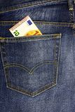 In the pocket of dark jeans inserted banknote 10 euro. In the pocket of dark blue jeans inserted banknote 10 euro royalty free stock photos